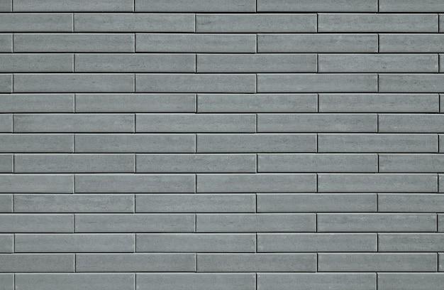 Textura de parede feita de tijolos decorativos cinza