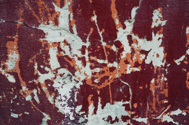 Textura de parede vermelha com tinta descascando