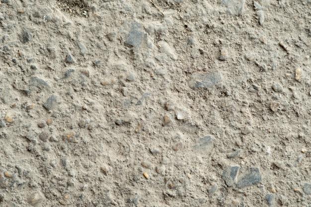Textura de pavimento de asfalto cinza escuro com pequenas pedras.