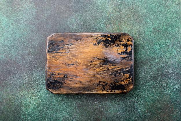 Textura de pedra concreta verde do fundo com placa de corte de madeira velha. vista do topo.