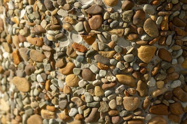 Textura de pedras do mar. um balde, colado com pedras do mar multicoloridas.