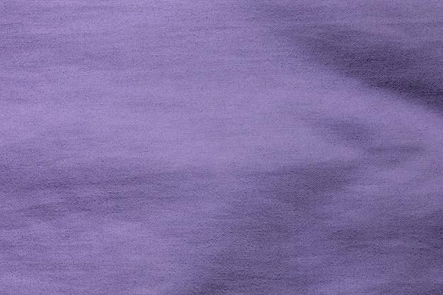 Textura de poliéster de pano de tecido roxo e fundo de matéria têxtil.