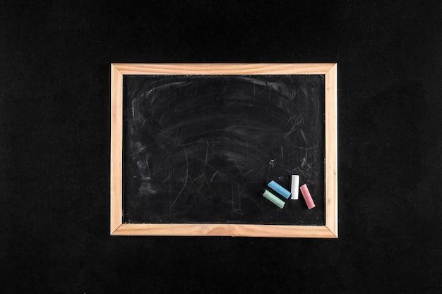 Textura de quadro negro sujo com pedaços de giz de cores diferentes, espaço de cópia