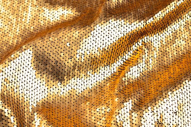 Textura de tecido de lantejoulas douradas.