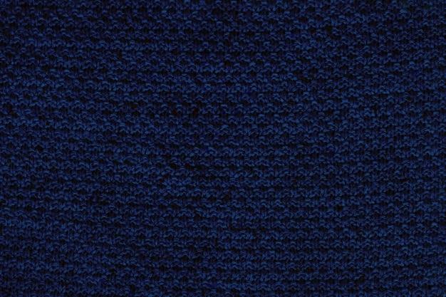 Textura de tecido de malha azul escuro. fundo de suéter áspero