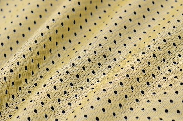Textura de tecido de roupa esporte jersey amarelo e fundo com muitas dobras
