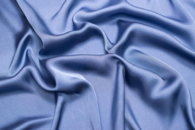 Textura de tecido de seda azul ou cetim de luxo. vista do topo.