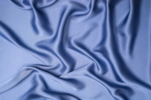 Textura de tecido de seda azul ou cetim luxuoso