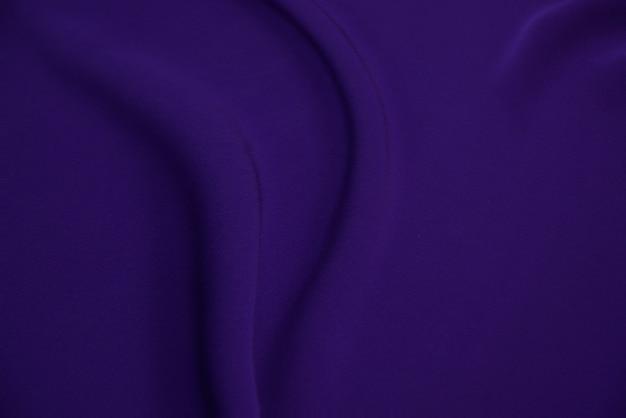 Textura de tecido de seda luxuosa de cetim roxo violeta ondulado elegante e elegante com fundo violeta