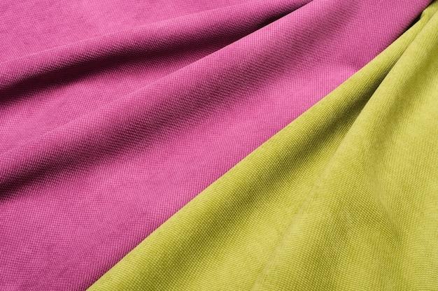 Textura de tecido de veludo rosa e verde. fundo abstrato de curvas de tecido de veludo