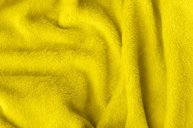 Textura de tecido fofo iluminador amarelo. fundo amassado cobertor de peles artificiais têxteis. tendência de cor do ano