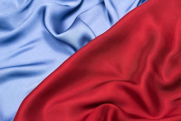 Textura de tecido luxuoso de seda ou cetim vermelho e azul. vista do topo.