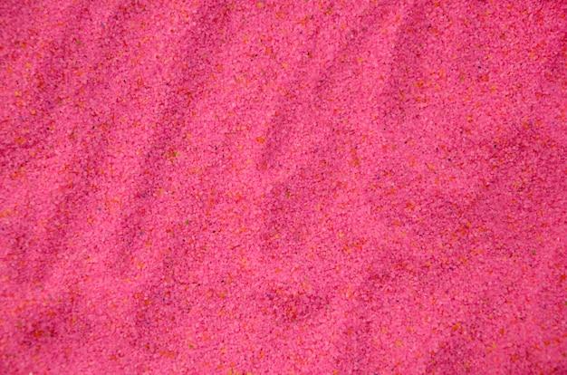Textura de um fim granulado colorido da areia acima. grãos cor de rosa
