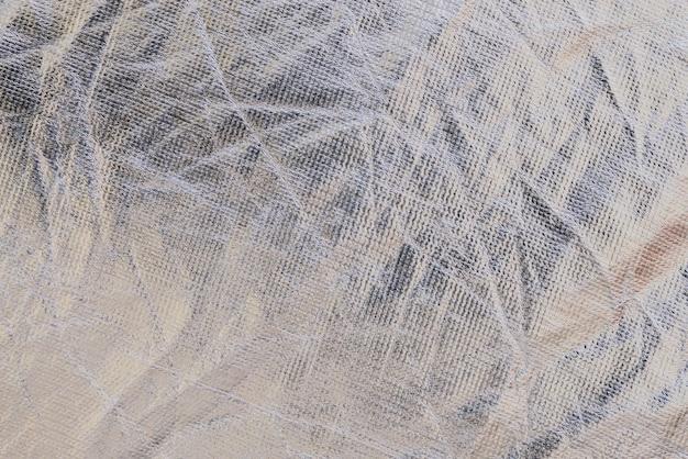 Textura de um fundo de tecido plástico enrugado metálico