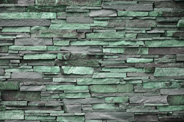Textura de um muro de pedra de pedras longas e difíceis de diferentes tamanhos e tons