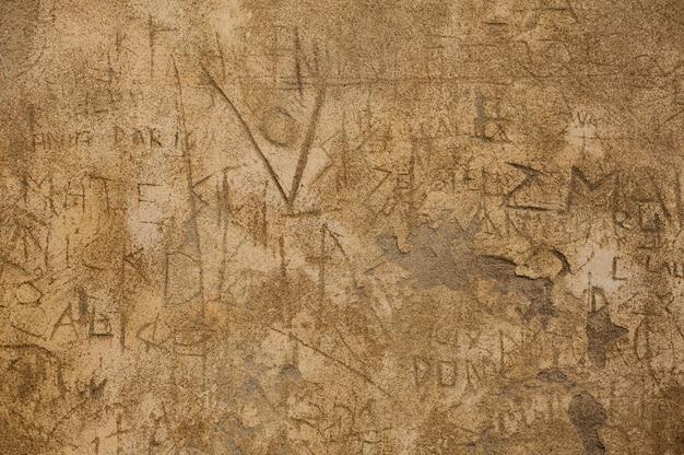 Textura de uma parede danificada pelo tempo e vandalizada em uma área suburbana