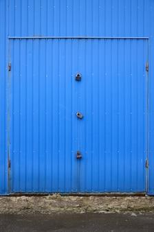 Textura de uma parede de metal azul com um portão fechado por três fechaduras