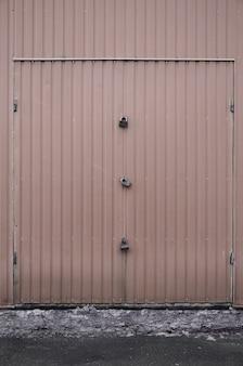 Textura de uma parede de metal marrom com um portão fechado por três fechaduras