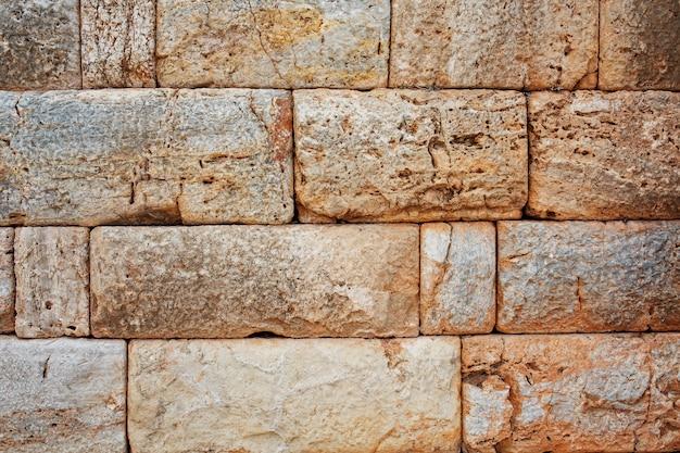 Textura de uma parede de pedra feita de grandes blocos, elementos da construção da antiguidade antiga.