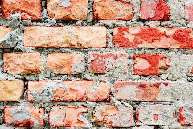 Textura de uma parede de tijolos com rachaduras e arranhões fundo