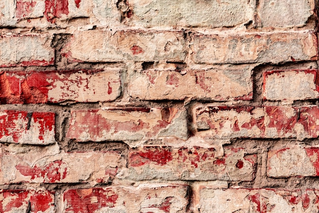 Textura de uma parede de tijolos com rachaduras e arranhões que podem ser usados como pano de fundo