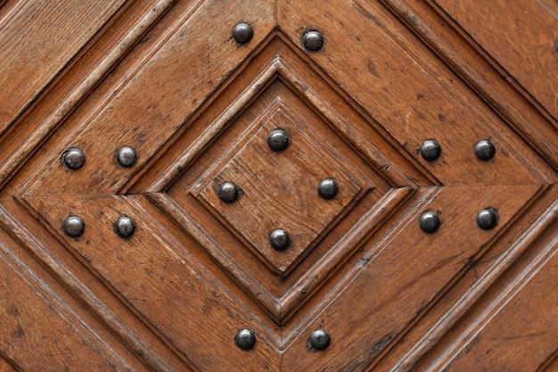 Textura de uma porta de madeira com rebites de metal. padrão de diamante de madeira