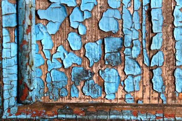 Textura de uma velha parede de madeira com fundo abstrato de tinta azul descascada.