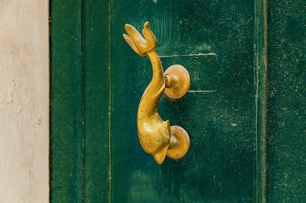Textura de uma velha porta de madeira com puxadores de metal na forma de um golfinho na ilha de malta