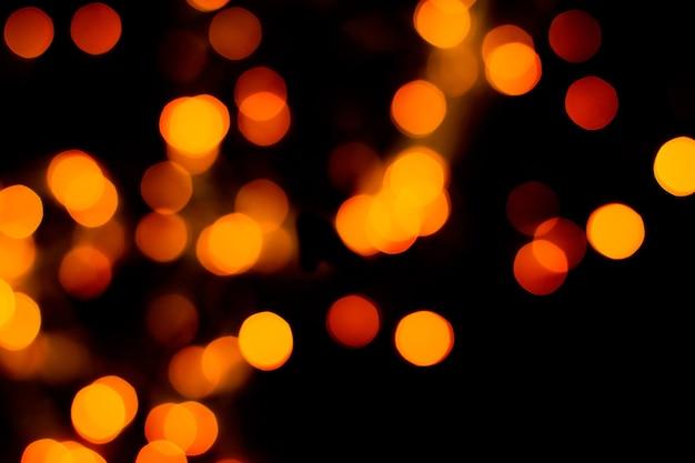Textura desfocada com purpurina dourada e luzes de natal desfocadas no preto