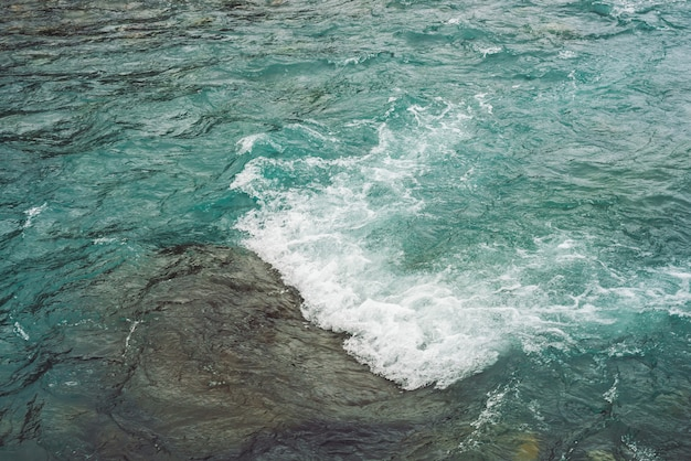 Textura detalhada da superfície da água correndo turquesa.
