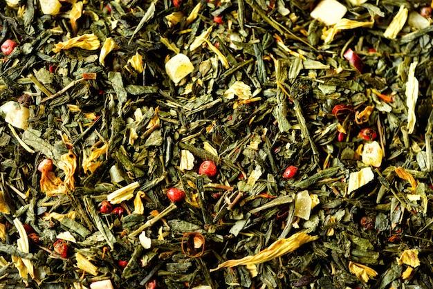 Textura do chá verde com as flores amarelas secadas das pétalas e pimenta vermelha. comida. folhas ervais saudáveis orgânicas, chá da desintoxicação.