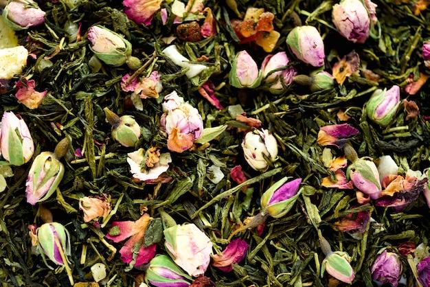 Textura do chá verde com pétalas cor-de-rosa. close up secado da textura dos rosebuds. comida. folhas ervais saudáveis orgânicas, chá da desintoxicação.