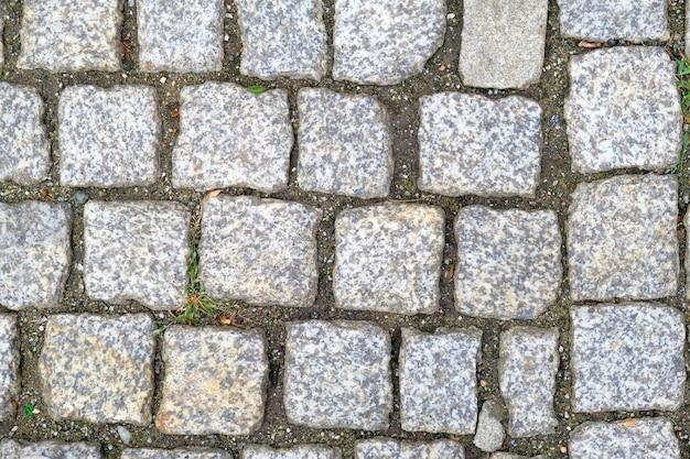 Textura do close-up cobbled velho do pavimento. fundo abstrato granito.