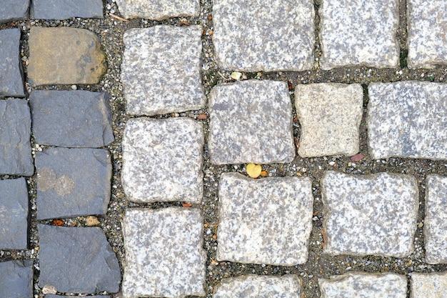 Textura do close-up cobbled velho do pavimento. fundo de pedra de granito.