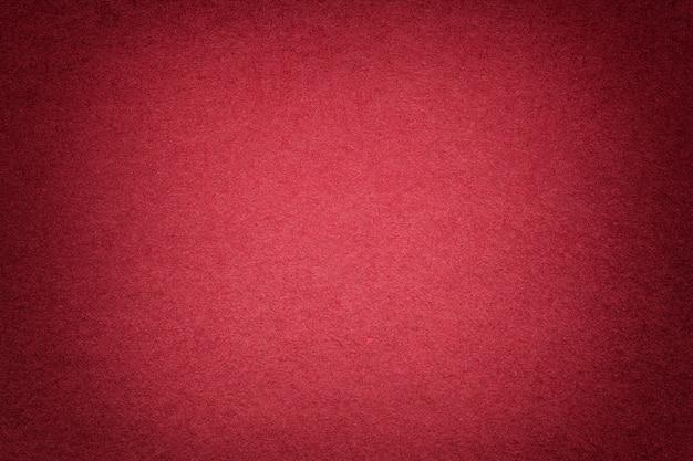 Textura do fundo de papel vermelho brilhante velho, close up. estrutura de papelão denso.