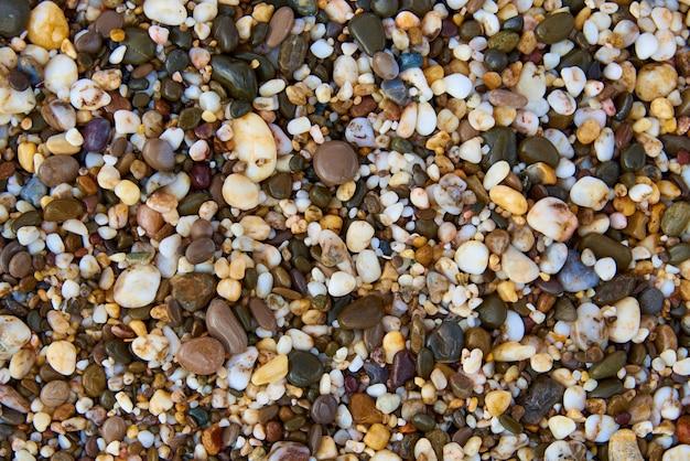 Textura do fundo de pedras coloridos molhadas na praia.