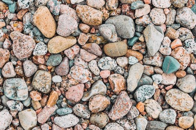 Textura do fundo de pedras redondas da praia do granito.
