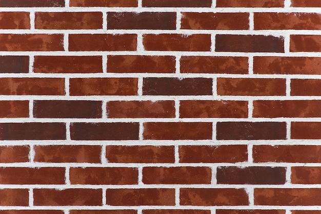 Textura do fundo de tijolos e do almofariz velhos do victorian. parede de tijolos vermelhos escuros com costura branca.