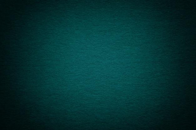 Textura do fundo escuro velho do papel de turquesa, close up. estrutura de papelão azulado profundo denso.