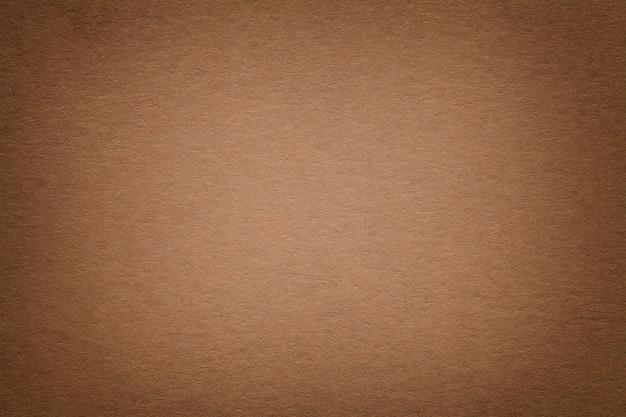 Textura do fundo velho do papel marrom escuro, close up. estrutura de papelão denso.