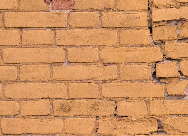 Textura do velho tijolo amarelo pintado de cor