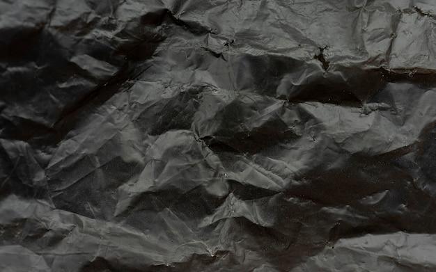 Textura e fundo de saco plástico preto, saco de lixo corrugado em alta resolução, fragmento de close-up da superfície de um saco de lixo preto amassado de polietileno como composição da textura do pano de fundo