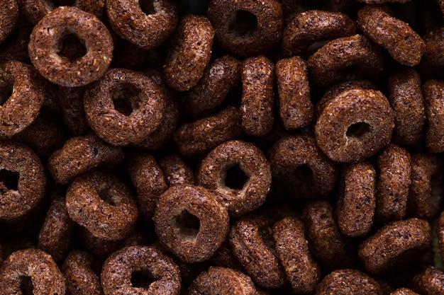 Textura e superfície de anéis de chocolate secos no café da manhã de cereais.