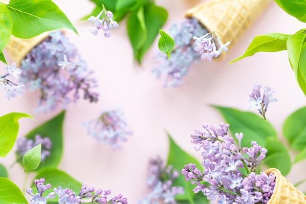 Textura fresca da primavera de flores lilás com copos de bolacha para sorvete em voo a voar. conceito de floração de primavera
