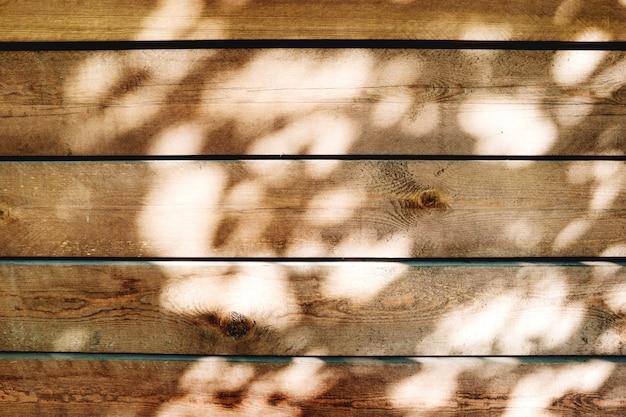 Textura gasto de placas de madeira com manchas de luz solar.