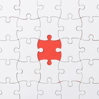 Textura inacabado do enigma de serra de vaivém no fundo vermelho.