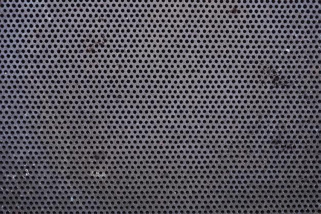 Textura metálica de close-up com pequenos furos, textura abstrata