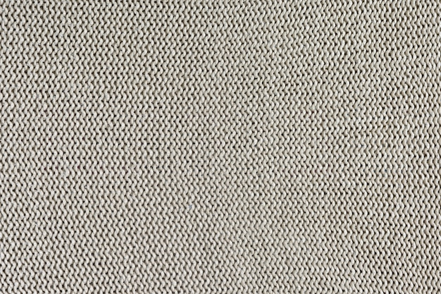 Textura monocromática de tricô. fundo bonito com loops. o produto tricotado é bege claro.
