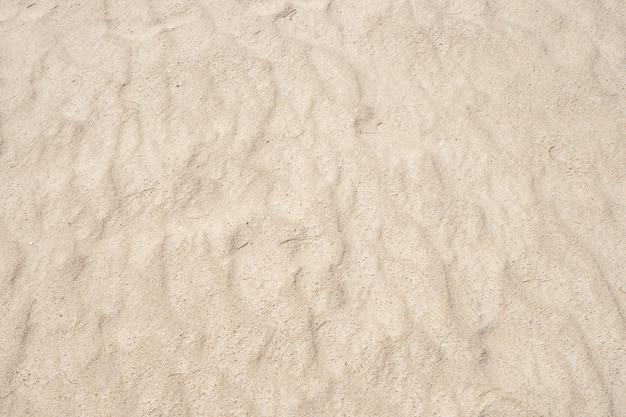 Textura natural da praia de areia com curva de onda de areia na praia em dia ensolarado imagem para o fundo de viagens da natureza summer design concept.