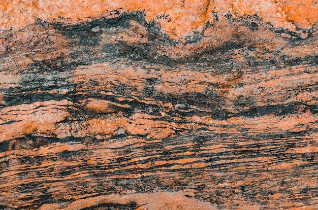 Textura ondulada de tonalidade vermelha de pedra de granito e listras escuras.